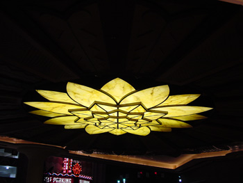 A flower shaped stained glass dome shines with yellow light