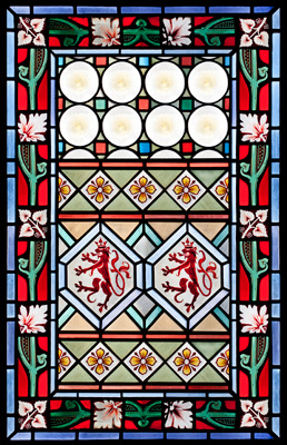 A mix of geometric and floral patterns make up this stained glass panel.