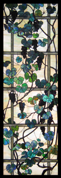 A stained glass panel featuring a trellis and grape vines.