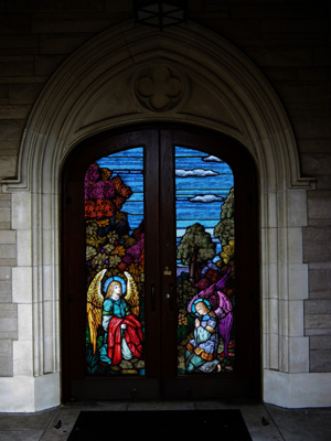 A door to a church is decorated with stained glass panels featuring angels. Make your church shine with stained glass inserts in your entry doors.
