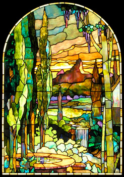 Mountains and trees are colorfully depicted in this Tiffany style stained glass window panel