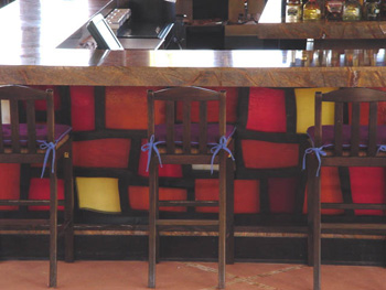 The front side of a seaside bar s covered in colorful stained glass