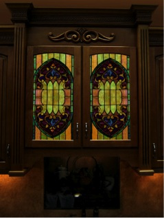 Colorful stained glass panels are pictured in a kitchen cabinet door. Stained glass adds color to your cabinets.