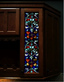 A simple cabinet door is decorated with a stained glass window insert that adds color and beauty to any kitchen.