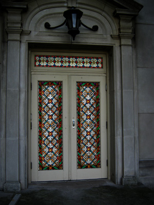 A stained glass door is topped with a beautiful matching transom window. We provide stained glass transom windows that are perfect for your project.